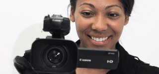 Young woman filming with camcorder